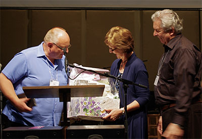"""Marilyn Hiebert receives a """"grandma"""" gift from BC Moderator Ron van Akker as husband Rudy looks on. And, oh - something in an envelope."""