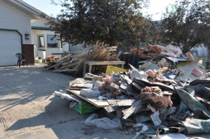 Sodden belongings piled on the street outside of a flood damaged home.