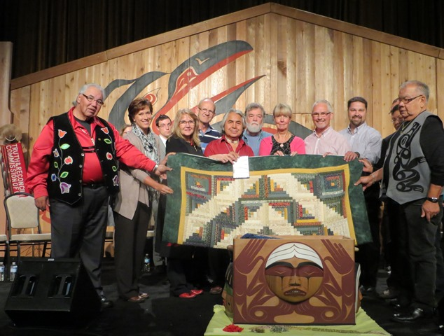"Mennonites offered an expression of reconciliation to their Aboriginal neighbours at the Truth and Reconciliation Commission's sixth National Event, Sept. 18-21, in Vancouver. The commission's mandate is to gather stories and raise awareness about the impacts of the residential school system on Aboriginal Peoples in Canada.   Representatives from the Mennonite community presented a quilt with a log cabin design as a symbol of warmth, friendship, healing, and peace. One Canadian frontier woman summarized the significance of these blankets: ""I make them warm to keep my family from freezing; I make them beautiful to keep my heart from breaking.""   Residential school survivor Isadore Charters (centre, in red), also gifted a copy of his 28-minute documentary Yummo Comes Home, which chronicles his story of healing and encounter with Jesus (www.outreach.ca).   Presenters included Dave Heinrichs of Eagle Ridge Bible Fellowship, Don Klaassen of Sardis Community Church, and Garry Janzen of Mennonite Church Canada. All expressions of reconciliation received during the seven national TRC events and placed in the ceremonial Bentwood Box will be permanently housed at the National Research Centre at the University of Manitoba.-LK"