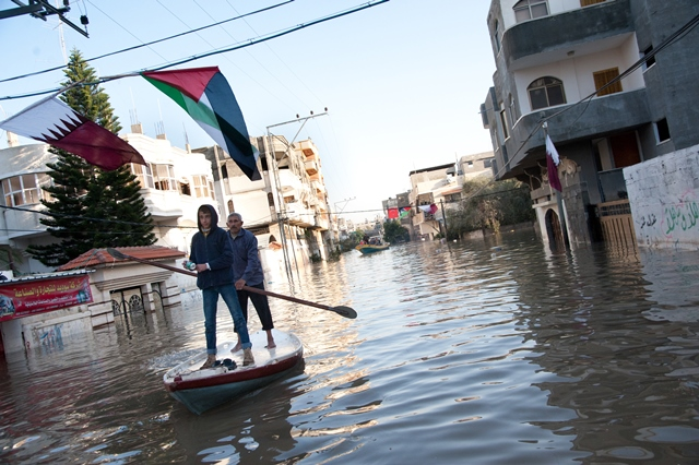A week after torrential rains caused floodwaters to reach about 12 feet, Palestinians use fishing boats to assist residents in retrieving belongings from homes along flooded streets in the Al Nafaq section of Gaza City, Dec. 18, 2013.