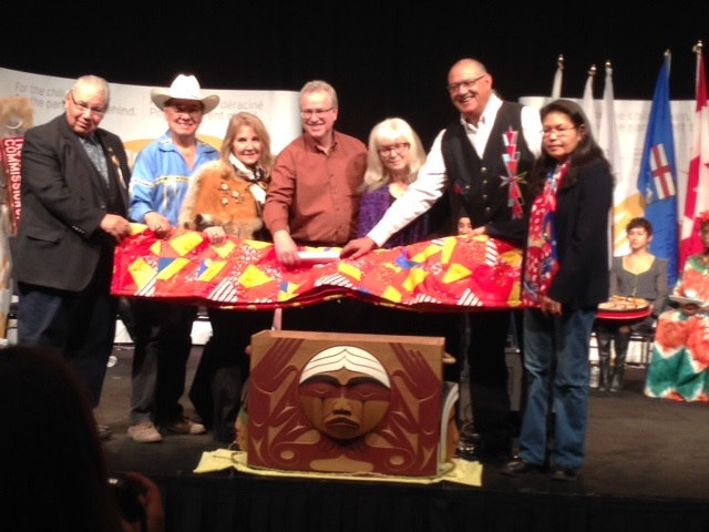 Anabaptist leaders present a blanket and a statement for inclusion in the Bentwood Box, a repository for offerings and commemorations at the Truth and Reconciliation Commission. Standing with the TRC Commissioners and survivor representatives is EMC ED Tim Dyck (centre) . PHOTO: courtesy MCC