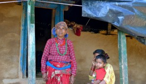 Mancauri Biswakarma stands outside her damaged house with her daughter Rita and grandson Roshi. After their other house collapsed in the earthquake, Mancaur's family of 10 must now live together in one room in this much-smaller house. Most of the roof collapsed and has been replaced with a tarp. (MCC Photo/Luke Reesor-Keller)
