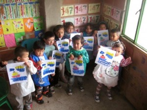 Children at Education Brings Hope show off their artwork for the camera. Education Brings Hope is a Global Family program that provides salaries, food and teaching supplies for a preschool and primary school of the Colombian Mennonite Brethren Church. Credit: Colombia Mennonite Brethren Church