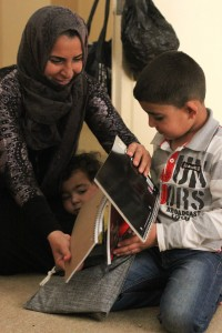 Asar and her sons Musab and Abdilbari open an MCC school kit they will use at an after-school educational program they attend in Jordan. The Syrian family has been in Jordan since 2014, but her husband can only find work a few days a month. Their last names are not used for their security. (Photo courtesy of Jane Ellen Grunau)