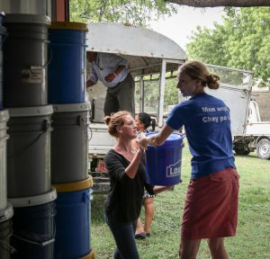 Rebecca Shetler Fast (in blue), MCC country representative, and Elise Quiring (in black), Connecting Peoples coordinator, help to load relief kits from storage onto the truck that will carry the kits to MCC's partner SAKALA in Cité Soleil, a neighborhood in Port-au-Prince. Twenty families are sheltering in SAKALA's community center after flash flooding from Hurricane Matthew forced them from their homes. Some of the families' homes were completely washed away in the storm. MCC Haiti provided relief kits, blankets, water purification and food to them. (MCC photo/Paul Shetler Fast)