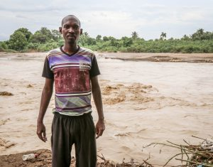 """Hudson Reny-Jean stand beside the River Gris that washed away homes in the Voudray community of Cite Soleil. The flooding also affected the safety of drinking water, making the water purification tablets that MCC provided a blessing, according to Reny-Jean.""""He held these 3-cent tablets in his hand and just kept repeating, 'These are such a blessing, these are such a blessing for our community."""" (MCC photo/Paul Shetler Fast)"""